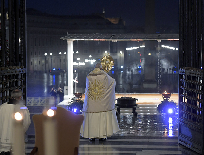 "Holding the Blessed Sacrament in a monstrance, Pope Francis stands before an empty St. Peter's Square — and a large TV, radio and internet audience worldwide — as he blesses ""the City (of Rome) and the World"" (Urbi et Orbi) Friday."