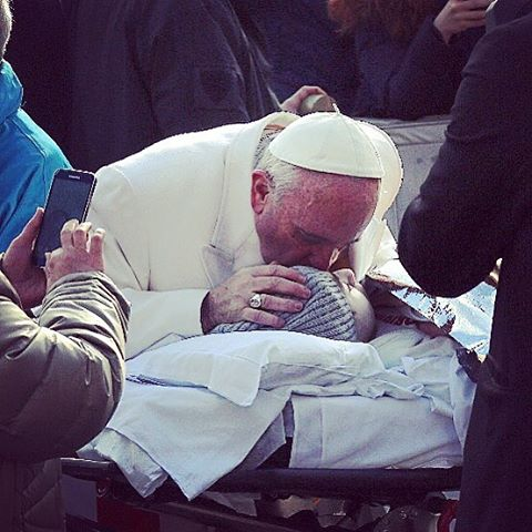 Pope Francis kisses a child who is bedridden on Feb. 10, Ash Wednesday, in St. Peter's Square.