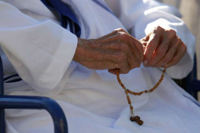Missionary of Charity sister prays the Rosary.