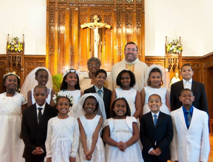 Father Christopher Walsh, shown with first communicants, says his close-knit Philadelphia parish of St. Raymond of Penafort is seeing collections up 2% from last year.