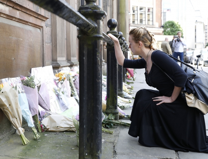 A woman prays May 23 as she views floral tributes left outside St Ann's Church, Manchester, following the Manchester Arena bomb attack. The attack killed 22 people, including children, and injured dozens more in the worst terrorist incident to hit Britain since the July 7, 2005, atrocities.