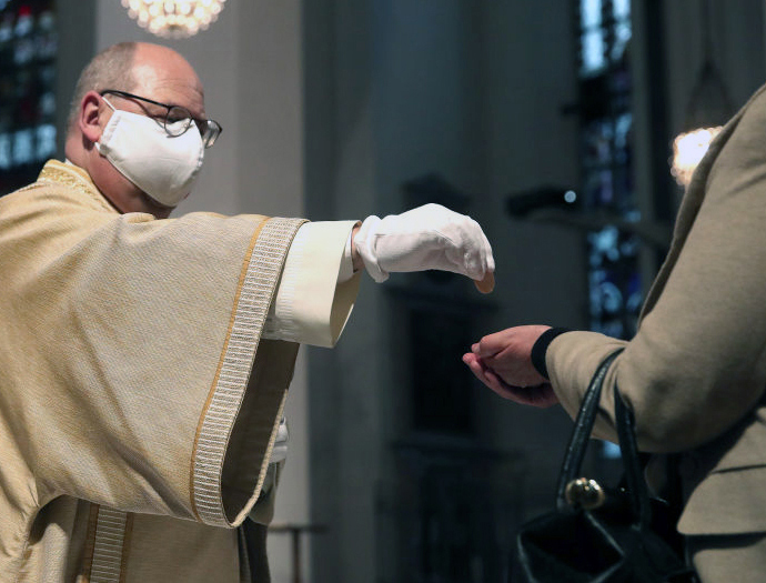 A deacon distributes Holy Communion during Mass Monday at the Frauenkirche (Cathedral of Our Lady) in Munich, Germany, the first day since March that churches were open in Bavaria. Nationwide state and local governments are easing lockdown measures that were imposed in order to stem the spread of the new coronavirus.