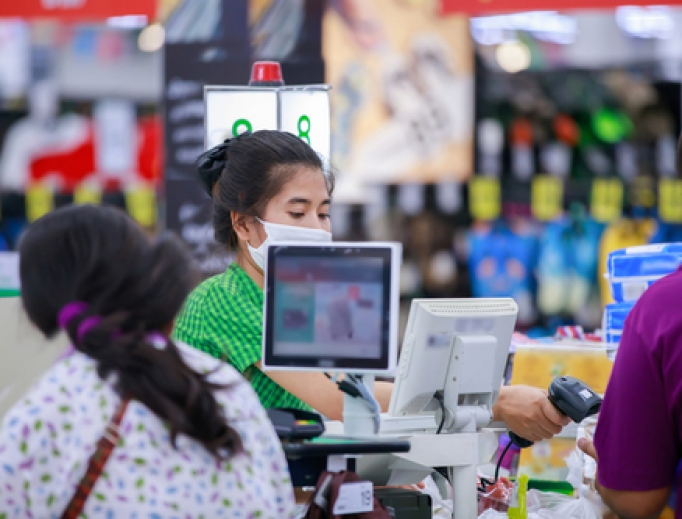 Store clerk wearing a mask checks out customers at a grocery store.