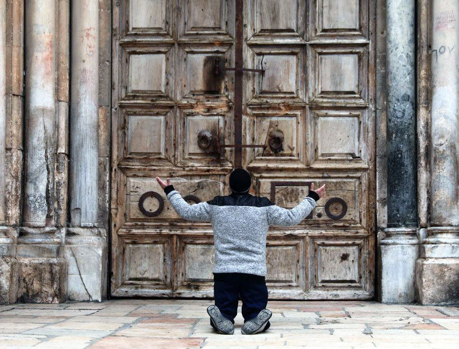 A man kneels in prayer in front of the closed doors of the Church of the Holy Sepulcher in Jerusalem April 9, during the COVID-19 pandemic lockdown.