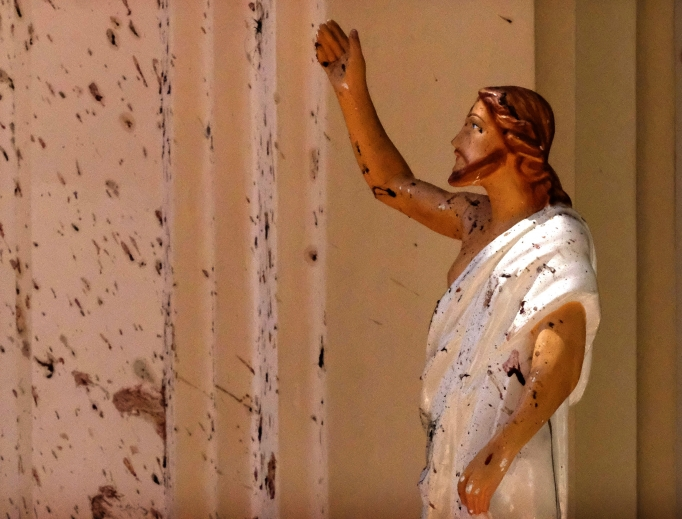Blood stains are seen on the wall and on a Jesus Christ statue at St. Sebastian's Church April 21 after a blast in Negombo, north of Colombo, Sri Lanka. Sri Lankan authorities blame a militant group for coordinated Easter bombings that ripped through Sri Lankan churches and luxury hotels, killing and injuring hundreds of people. It was Sri Lanka's deadliest violence since a devastating civil war in the South Asian island nation ended a decade ago.