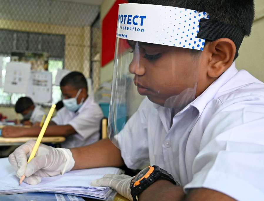 A student wearing a face shield sits in a classroom after their school was reopened in Colombo, Sri Lanka, July 6.