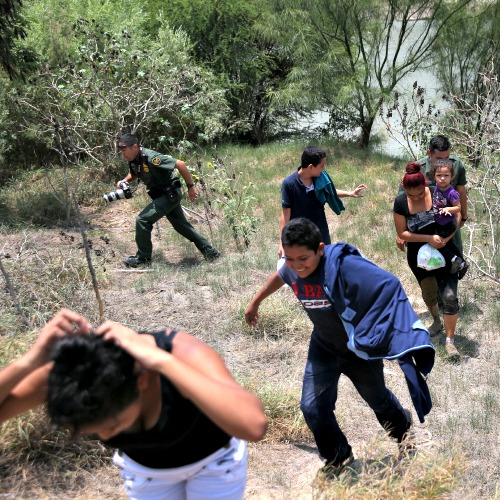 U.S. Border Patrol agents escort unaccompanied minors and immigrant families from El Salvador after they crossed the Rio Grande illegally into the United States on July 24 in Mission, Texas.