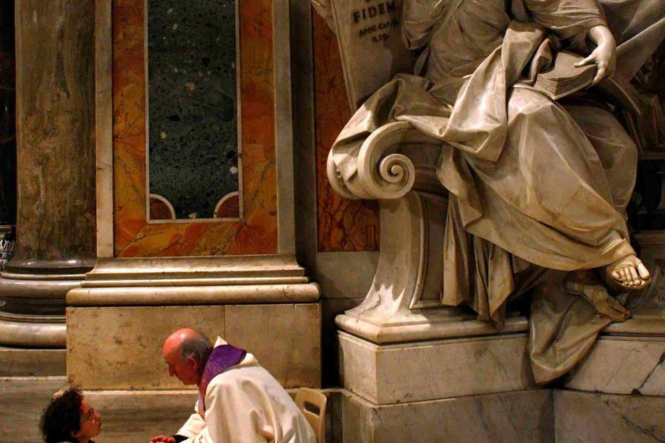 A priest hears a confession during a penitential celebration at St. Peter's Basilica.