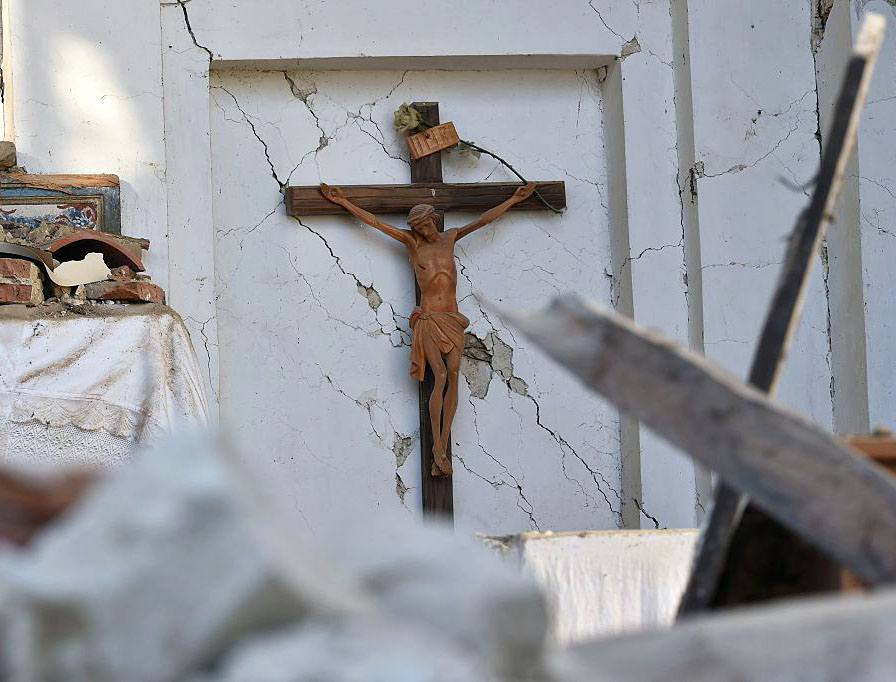 A picture taken on August 27, 2016 shows a crucifix in a damaged church in San Lorenzo, near the Italian village of Amatrice, three days after a 6.2-magnitude earthquake struck the region.