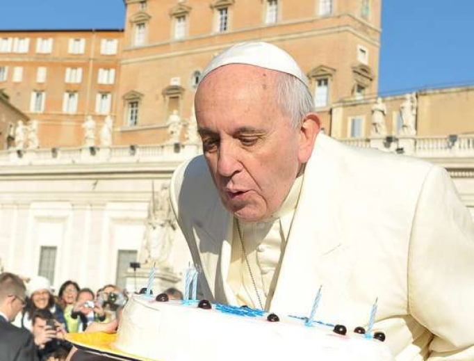 Pope Francis blows out candles on a birthday cake at his Dec. 17, 2014, audience.