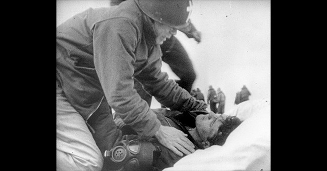 Lieutenant Commander Joseph T. O'Callahan, USNR(ChC) prepares to anoint an injured crewman aboard USS Franklin (CV-13), after the ship was set afire by a Japanese air attack, 19 March 1945. The crewman is reportedly Robert C. Blanchard, who survived his injuries. (Credit: Naval Historical Center)