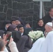 Pope Francis receives white roses from nuns during surprise visit Feb. 14.