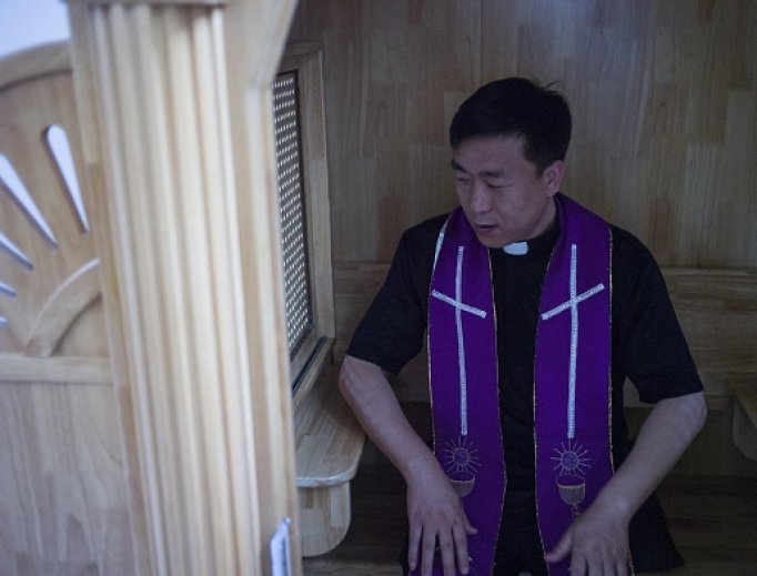 Chinese priest Lin Xiuqiang poses for a photograph in his Catholic church in Tianjin. Dozens of church buildings have been demolished and crosses removed in recent months.
