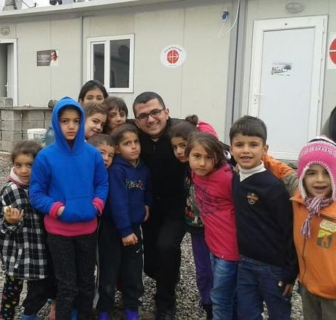Seminarian Remi Marzina Momica with a group of children outside an Aid to the Church in Need office.