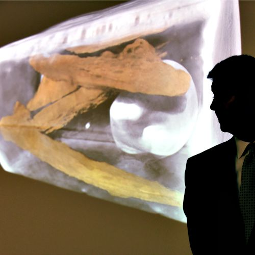 Randall Kremer, director of public affairs at the Smithsonian's National Museum of Natural History, stands next to an image showing the contents of a well-preserved silver box believed to be a Catholic reliquary, during a news conference in Washington, on July 28. The box was found resting on top of the coffin of Capt. Gabriel Archer at the site of the 1608 Anglican church at the historic Jamestown colony site in Virginia. It is believed that the box contains seven bone fragments and two pieces of a lead ampulla, a container used to hold holy water.