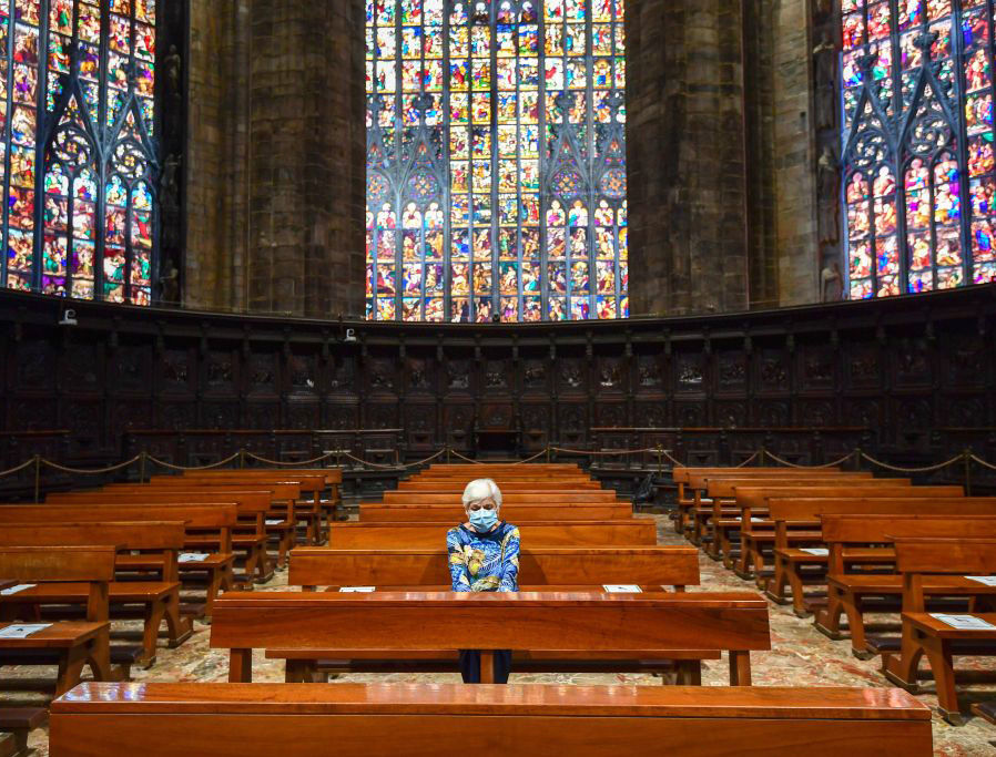 A woman attends Mass at the Cappella Feriale of the Duomo cathedral in Milan on Monday.