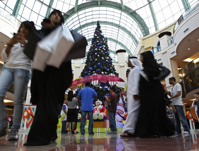 An Emirati couple and people of other nationalities pass by a giant Christmas tree at a shopping mall in Dubai, United Arab Emirates. Pope Francis will make the first papal visit to the Arabian Peninsula next month.