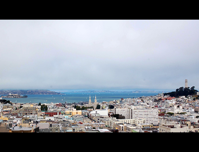 In this view of San Francisco, Alcatraz can be seen in San Francisco Bay on the left, Coit Tower occupies the hill on the right, and the twin spires of Sts. Peter and Paul are visible in the center of the photo.