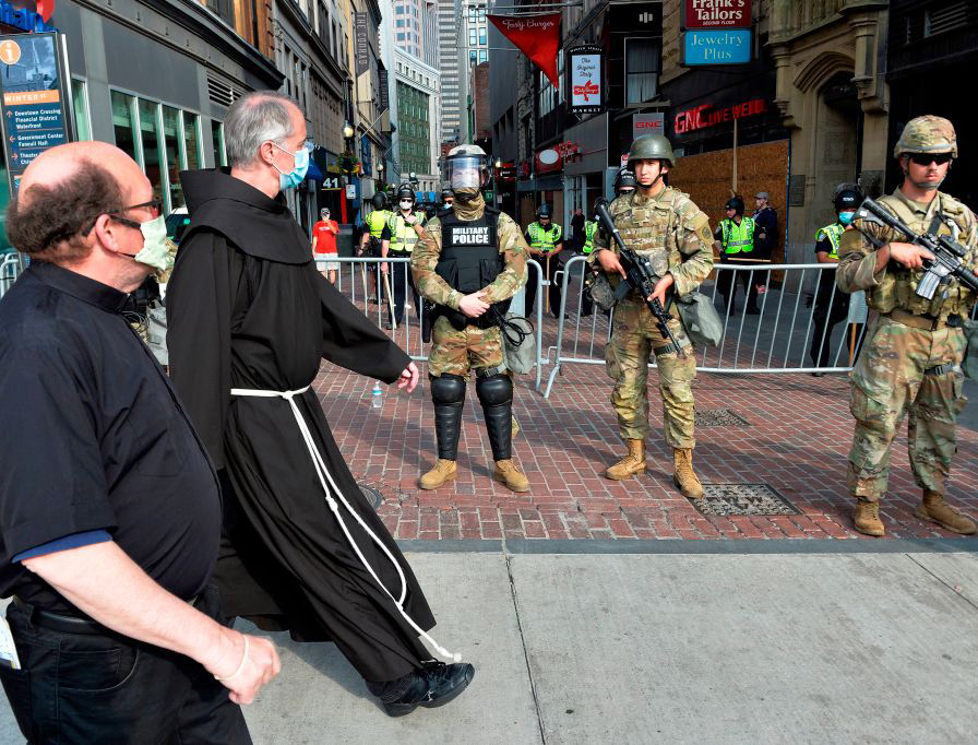 Two priests walk by National Guard Soldiers stationed in downtown Boston on Wednesday.