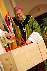 Bishop Jenky ties a ribbon around a crate of documents for Archbishop Sheen's cause.
