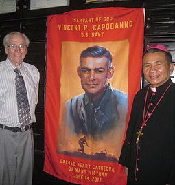 Ted Bronson and Bishop Joseph Tri stand in front of a banner of Servant of God Father Vincent Capodanno in Vietnam, June 2013.