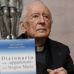 French Father Rene Laurentin, co-author of the Dictionary of Apparitions of the Virgin Mary, is seen next to the 1,600-page volume during a press conference to release the Italian edition in Rome Dec. 13. The book lists more than 2,400 claims of people who over the centuries have claimed to have seen Mary.