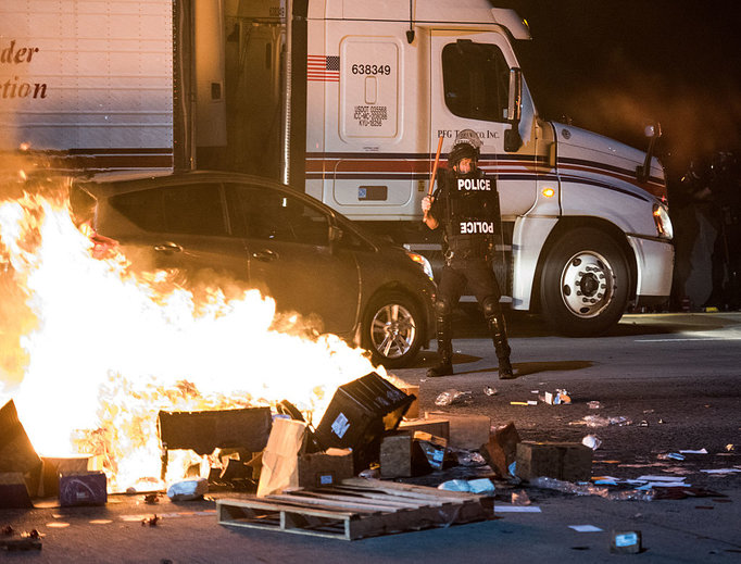 A police officer stands guard near a fire on the I-85 during protests in the early hours of Sept. 21 in Charlotte, North Carolina. The protests followed the fatal shooting of 43-year-old Keith Lamont Scott by a police officer at an apartment complex near UNC Charlotte.