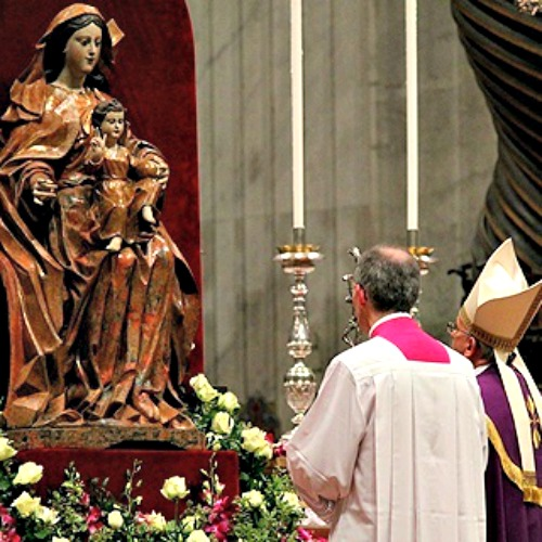 Pope Francis prays before a statue of Mary in St. Peter's Basilica.