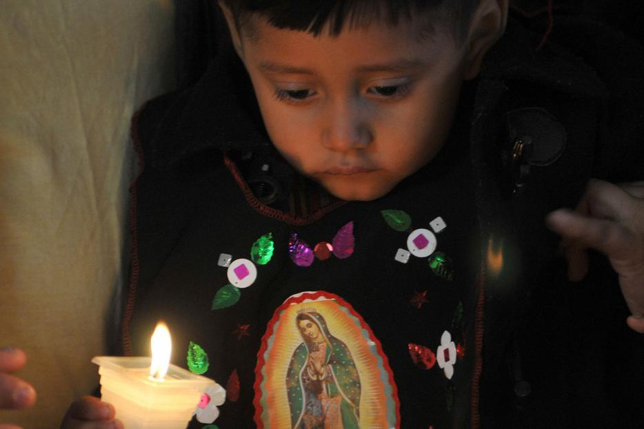 A boy lights a candle in the sanctuary of Our Lady of Guadalupe in Guatemala City, Dec. 12, 2008.