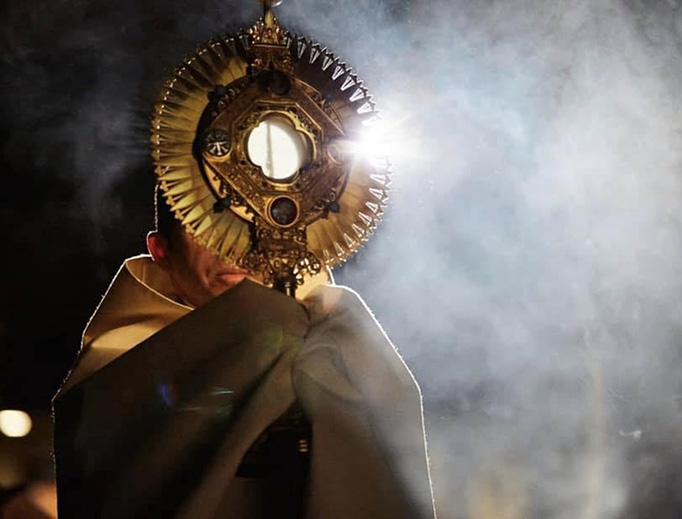 Father Michael Delcambre of Broussard, Louisiana, carries the Blessed Sacrament in procession.