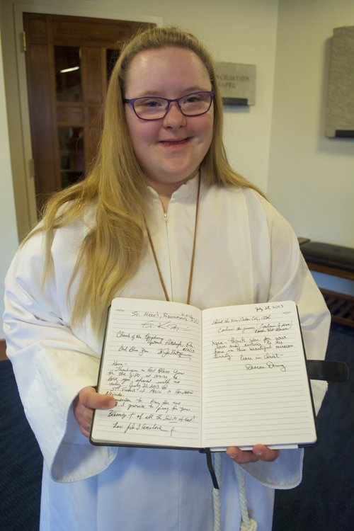 Kara Jackson, a young woman with Down syndrome who wants to serve Mass in all 50 states, in Northglenn, Colo. Kara's notebook filled with messages from priests documents her journey.