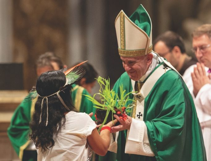 Pope Francis accepts a gift at the Mass for the closing of the Amazon synod Oct. 27.