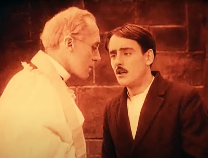 Father Fathley (A.W. McClure) hears the confession of The Boy (Robert Harron) in D.W. Griffith's 1916 movie Intolerance.