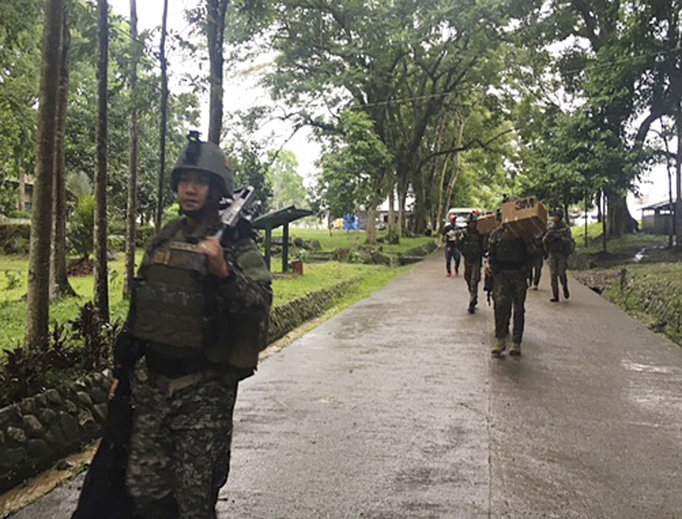 Philippine troops arrive at their barracks to reinforce fellow troops following the siege by Muslim militants May 24 on the outskirts of Marawi city in the southern Philippines. The militants burned buildings and took hostages.