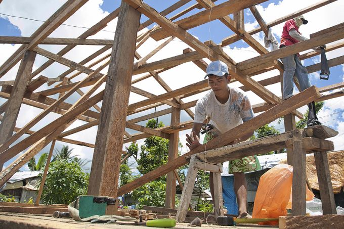 Men work to rebuild homes in Visayas, Philippines, in the aftermath of Typhoon Haiyan.