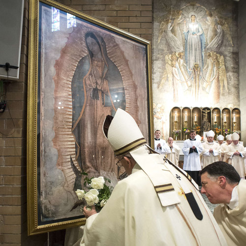Pope Francis places a bouquet of roses in front of Our Lady of Guadalupe image at the conclusion of Mass celebrated at the Pontifical North American College in Rome on May 2, 2015.