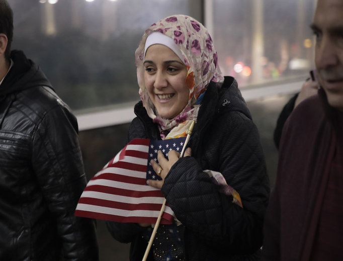 Syrian refugee Baraa Haj Khalaf clutches an American flag as she leaves O'Hare Airport with her family after arriving on a flight from Istanbul, Turkey, on Feb. 7 in Chicago. She arrived in the United States with her husband and daughter after spending five years in a refugee camp in Turkey. She was allowed to enter due to the temporary halt to the executive order.