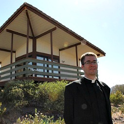 Father Eugene Florea stands in front of a newly built hermitage.