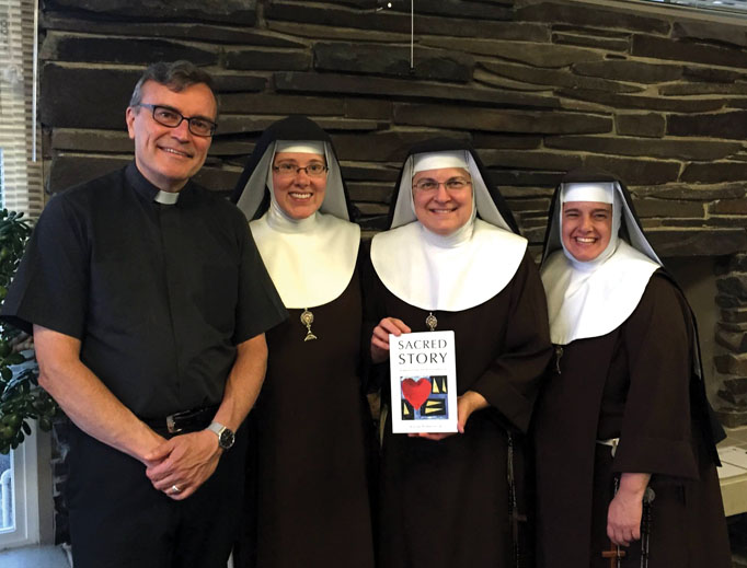 Father Bill Watson, shown with Poor Clares of Perpetual Adoration from the Monastery of St. Michael the Archangel, and his Sacred Story Institute promote Ignatian spirituality.