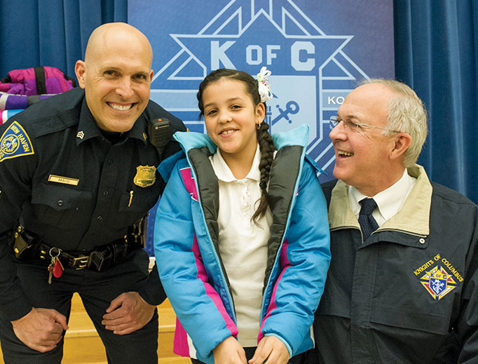 Supreme Knight Carl Anderson and New Haven police distribute coats during a 2016 'Coats for Kids' event at a local school.