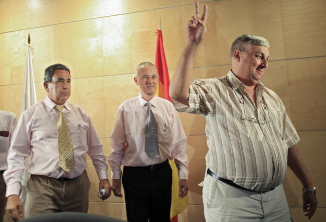 FREE BUT EXILED. Released Cuban political prisoner Ricardo Gonzalez gestures next to Julio Cesar Galvez, left, and Omar Ruiz as they arrive for a news conference at Barajas airport in Madrid July 13. The men were among seven former political prisoners who arrived in Madrid with their families — the first of 52 dissidents the Cuban government has promised to free in a historic policy shift.