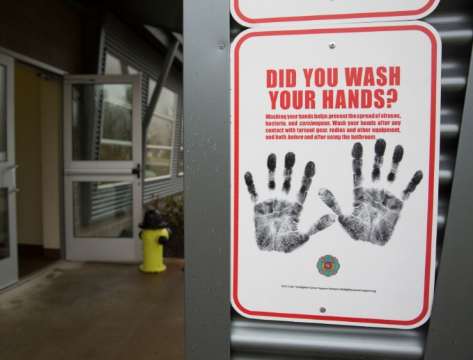 Above, a sign reminding people to wash their hands is pictured outside a dormitory at the Washington State Patrol Fire Training Academy, which has been designated as a coronavirus quarantine site for travelers from Hubei Province, China. Below, Dr./Deacon Timothy Flanigan sanitizes his hands at a Liberia medical clinic. Dr. Flanigan is an infectious disease specialist at the medical school at Brown University and assisted with the recent Ebola outbreak.