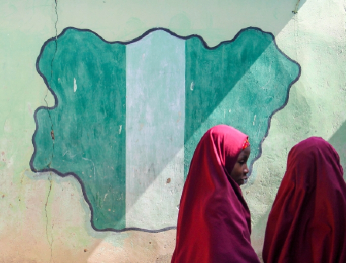 Students pass a classroom with the map and flag of Nigeria painted on it, at Success Private School, one of the first schools attacked by Boko Haram in 2009 in Maiduguri, Nigeria, 2015.