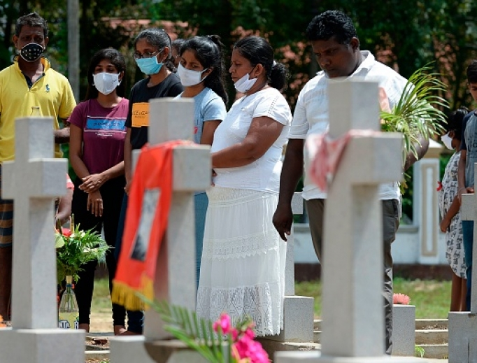 Relatives pay their respects at a graveyard for St. Sebastian's Church bomb blasts victims in Negombo on April 21, 2020, to mark the first anniversary of the attacks.