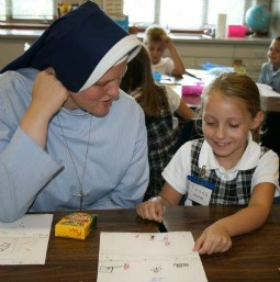Sister Regina Marie of the School Sisters of Christ the King talks with a young student.