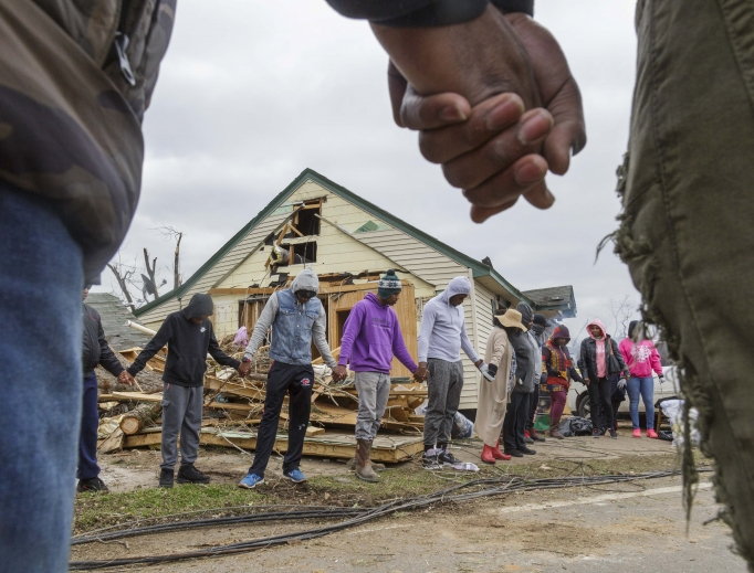 Residents of Talbotton, Georgia, pray together March 4 outside a home destroyed by a tornado; the moment of prayer came the day after storms battered Alabama and Georgia.