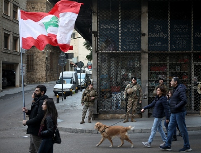 Army soldiers look on as Lebanese anti-government protesters march toward the capital in Beirut's downtown district Jan. 25. The political impasse is worsening an already-dire economic crisis in Lebanon that the World Bank says may see the number of people living in poverty climb from a third to half the population.
