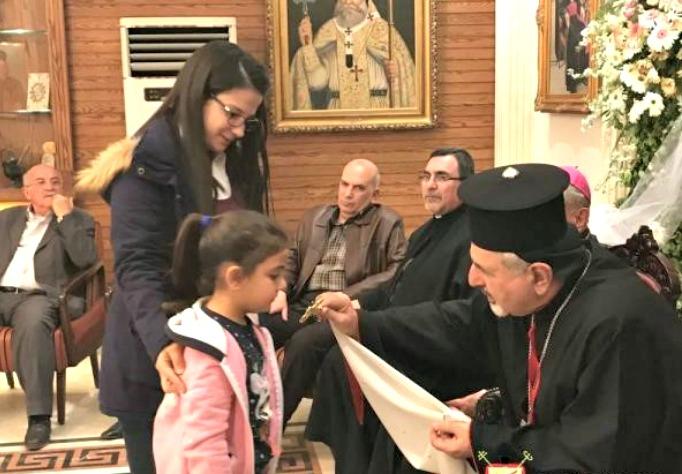 Patriarch Younan blesses a child in Aleppo, Syria.