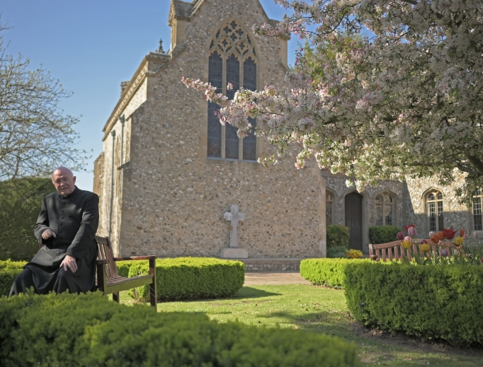Msgr. John Armitage, shown enjoying the garden and praying at the Walsingham shrine, says, 'Our Lady wanted us to make the dedication in the midst of this storm.'