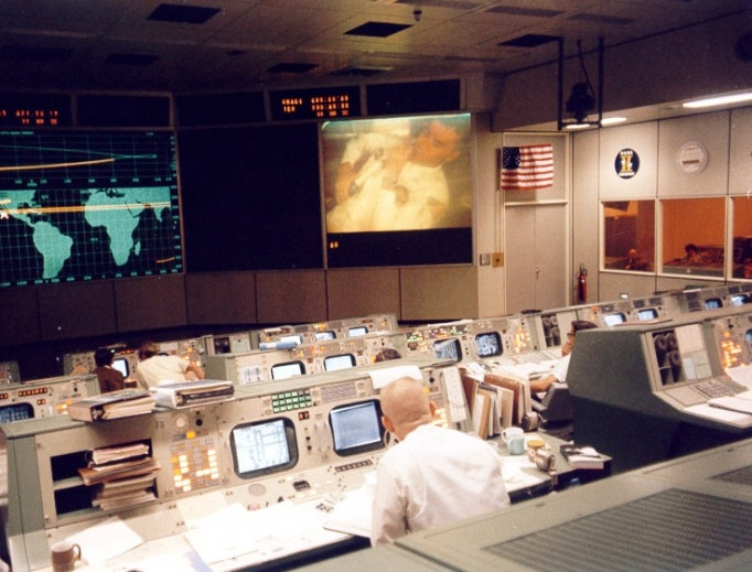 Above, mission control is seen during the perilous mission: Catholic flight director Gene Kranz, with his back to the camera at right center, watches a TV transmission from the Apollo 13 crew moments before the accident that crippled the mission on April 13, 1970. Astronaut Fred Haise can be seen on the large screen at the upper right.